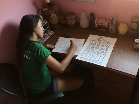 Senior Lauren Rodriguez concentrating on drawing flowers in a room scene while listening to music.
